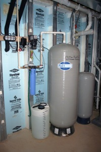 Rainwater harvesting mechanics inside the home include chlorine and pressure tanks, a changeable cartridge filter and low level indicator light.